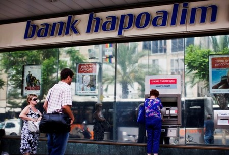 FILE PHOTO: A woman uses an ATM outside a Bank Hapoalim branch in Tel Aviv