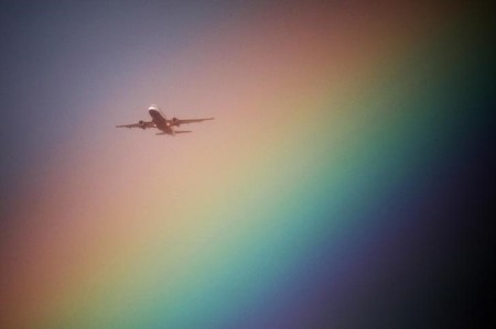 An aeroplane flys near a rainbow on its way to Heathrow Airport in London, Britain