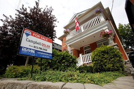 FILE PHOTO: A real estate sign is seen in front of a house for sale in Ottawa