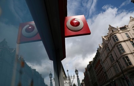 A branded sign is displayed on a Vodafone  store in London