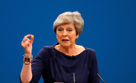 Britain's Prime Minister Theresa May holds up a cough sweet after suffering a coughing fit whilst  addressing the Conservative Party conference in Manchester