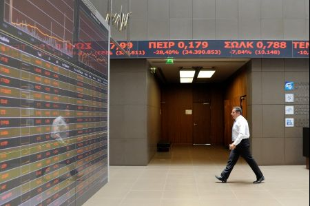 An employee walks under stock ticker showing stock options inside Athens stock exchange building in Athens