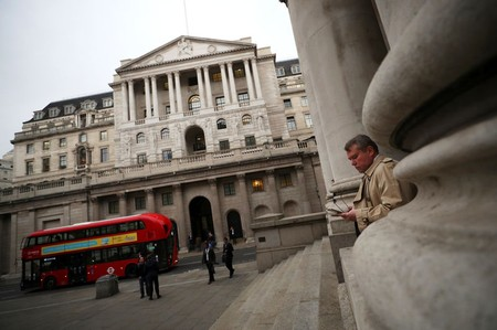 A man holds his mobile phone outside the Bank of England in London