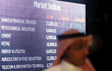 FILE PHOTO:  A trader stands in front of a screen displaying stock information at the Saudi Stock Exchange (Tadawul) in Riyadh