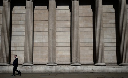 FILE PHOTO: A pedestrian walks past the Bank of England in the City of London
