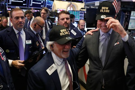 Thomas Farley, president of the New York Stock Exchange, laughs with trader Peter Tuchman as they wear hats to celebrate the DJIA rising above 23,500 on the floor of the New York Stock Exchange in New York
