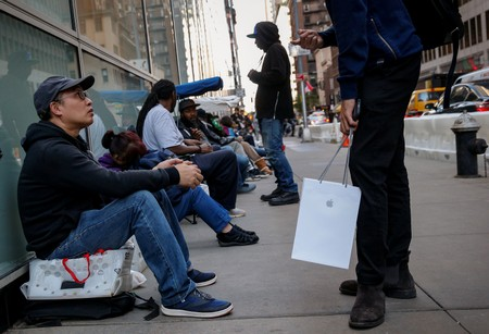 Customers wait in line for the new iPhone X outside an Apple store in New York City