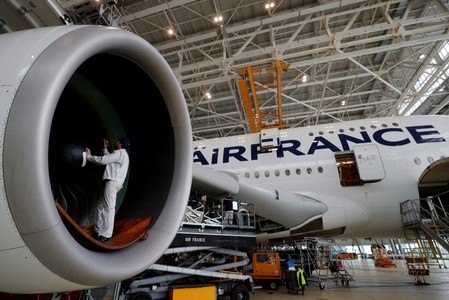 FILE PHOTO: An employee works on an Airbus A380 plane inside the Air France KLM maintenance hangar at the Charles de Gaulle International Airport in Roissy