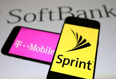 Smartphones with the logos of T-Mobile and Sprint are seen in front of a Soft Bank logo in this illustration