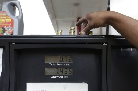 A gas station attendant piles up coins on top of a fuel dispenser at a gas station of state oil company Petroleos de Venezuela (PDVSA) before the government raised the price for fuel, in Caracas