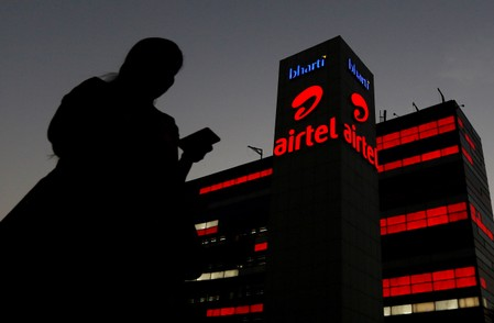 FILE PHOTO: A girl checks her mobile phone as she walks past the Bharti Airtel office building in Gurugram