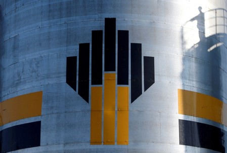 FILE PHOTO: Shadow of worker is seen next to logo of Russia's Rosneft oil company at central processing facility of Rosneft-owned Priobskoye oil field outside Nefteyugansk