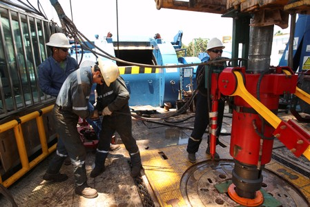 Oil field technicians work with a drill at an oil rig of Ecuador's state oil company Petroamazonas, in Tiputini