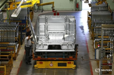 Men work at the assembly line in the truck production plant of truck and bus-maker MAN AG in Munich