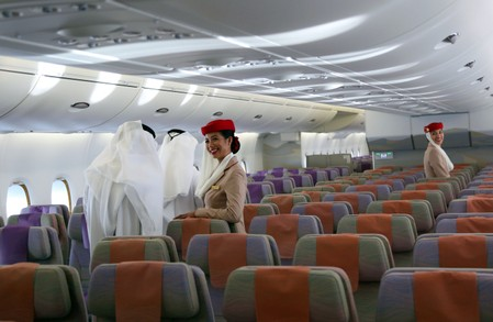 Fligt attendants look on as visitors tour an Airbus A380 of Emirates during the Dubai Airshow in Dubai