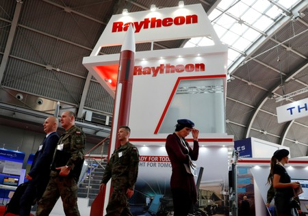 FILE PHOTO: People pass the U.S. defense company Raytheon stand at an international military fair in Kielce