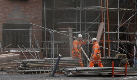Workers carry scaffolding on a construction site in Chester