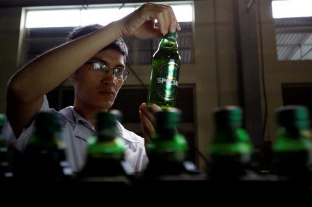 FILE PHOTO: A worker checks for faults on beer bottles which move along a production line in a factory of Saigon Beer Corporation in Hanoi