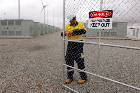 A worker checks the main gate for the compound housing the Hornsdale Power Reserve, featuring the world's largest lithium ion battery made by Tesla, during the official launch near the South Australian town of Jamestown