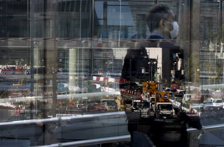 A construction site is reflected on a window as a businessman walks in Tokyo's business district