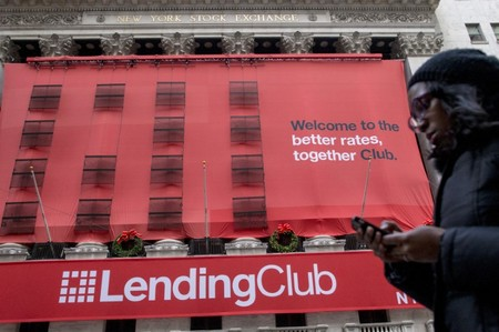 FILE PHOTO - A woman looks at her phone as she passes by a Lending Club banner on the facade of the the New York Stock Exchange