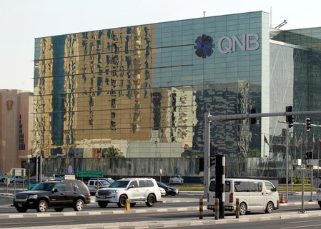 Cars drive past the building of Qatar National Bank (QNB) in Doha