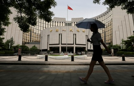 FILE PHOTO: Woman walks past the headquarters of the PBOC in Beijing