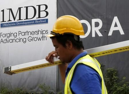 A construction worker walks past a 1Malaysia Development Berhad (1MDB) billboard at the Tun Razak Exchange development in Kuala Lumpur, Malaysia