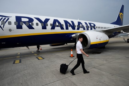 A pilot disembarks a Ryanair flight at Stansted airport in London