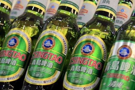 FILE PHOTO: Bottles of Tsingtao beer are placed on shelves at a supermarket in Shanghai