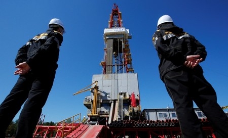 File photo of workers looking at drilling rig at well pad of Rosneft-owned Prirazlomnoye oil field outside Nefteyugansk