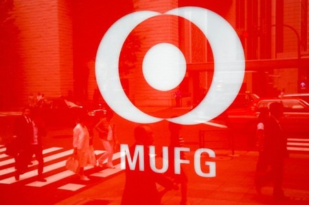 FILE PHOTO - People are reflected in the logo of Mitsubishi UFJ  Financial Group's bank of Tokyo-Mitsubishi UFJ in Tokyo