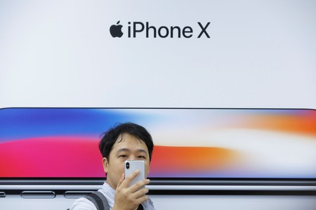 FILE PHOTO: An attendee uses a new iPhone X during a presentation for the media in Beijing