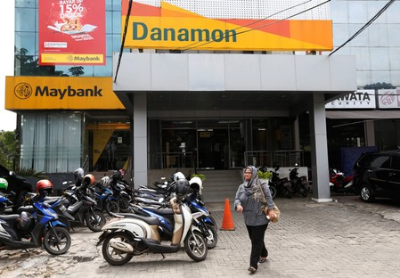 A woman walks in front of a Danamon Bank branch office in Jakarta, Indonesia