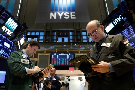 FILE PHOTO: Traders work on the floor of the NYSE in New York