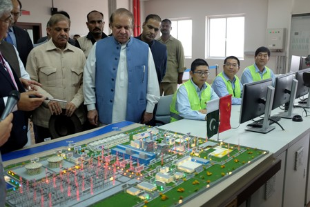 Pakistani PM Nawaz Sharif listens as experts explain a process of the Haveli Bahadur Shah LNG power plant during the inauguration in Jhang