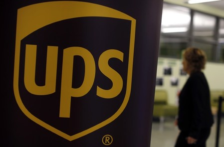Woman walks past a sign bearing the UPS logo at a job fair in Chicago