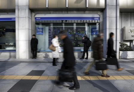 A pedestrian looks an electronic board showing the stock market indices of various countries outside a brokerage in Tokyo