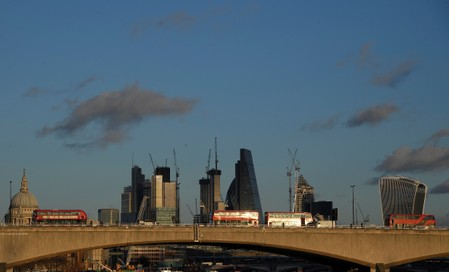 London buses cross Waterloo Bridge, with the City of London financial district seen behind in London, Britain