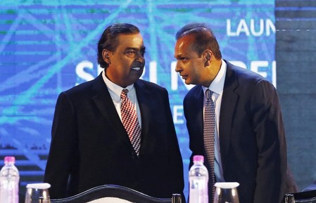 FILE PHOTO: Anil Ambani talks to his brother Mukesh during the launch of Digital India Week in New Delhi