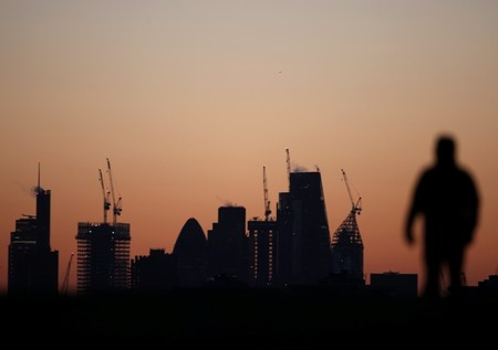 A man walks accross Primrose Hill as dawn breaks behind construction cranes in the City of London