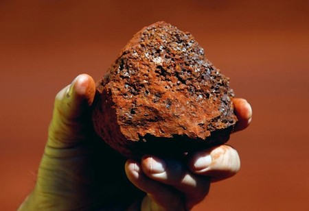 File photo of a miner holding a lump of iron ore at a mine located in the Pilbara region of Western Australia