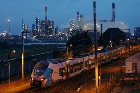 A TER train makes its way in front of the French oil giant Total refinery in Donges