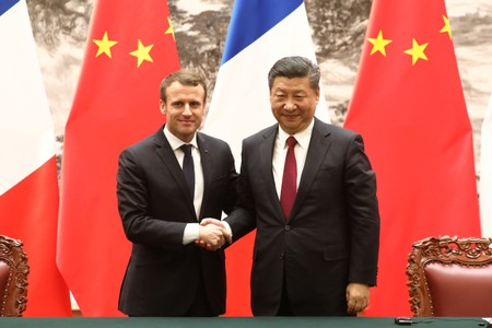 French President Emmanuel Macron and Chinese President Xi Jinping shake hands during a press conference in Beijing