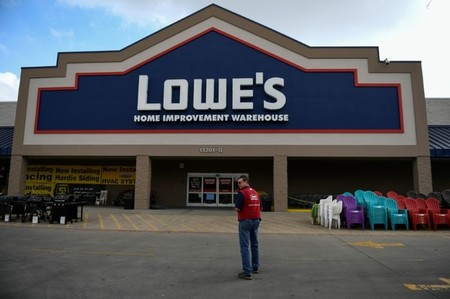 FILE PHOTO: An employee stands outside a Lowe's home improvement chain in Austin, Texas