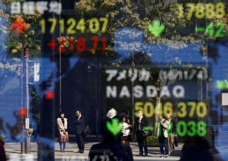 People are reflected in a display showing the Nikkei average and the NASDAQ average of the U.S outside a brokerage in Tokyo