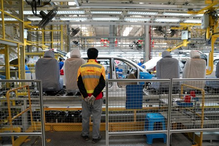 An employe of DHL works inside a Baojun car final assembly plant operated by General Motors Co and its local joint-venture partners in Liuzhou