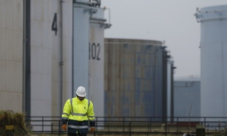A worker walks past oil tanks at the Total refinery in Grandpuits