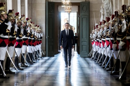 FILE PHOTO: French President Emmanuel Macron  walks through the Galerie des Bustes (Busts Gallery) to access the Versailles Palace in July 2017.