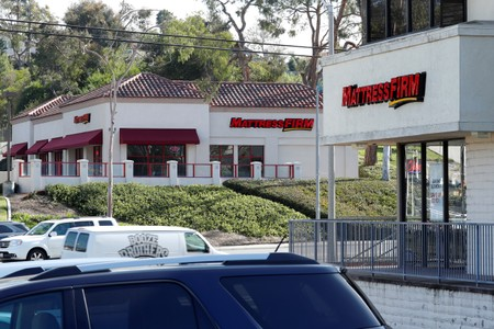 Two Mattress Firm stores are shown on either side of the street in Encinitas, California,